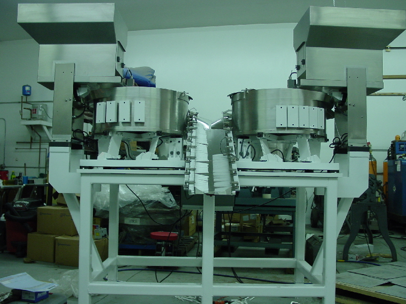 Pharmaceutical Feeders  feeding plastic parts, with table, controllers, hoppers and custom designed inline / escapement