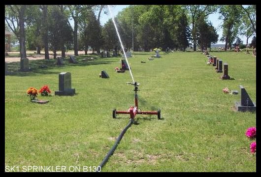 Waterreel sprinkler travels through cemetery