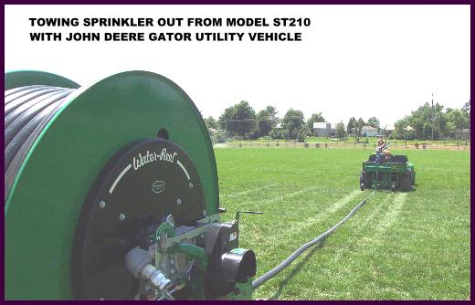 Sprinkler and cart being towed out with a John Deere Gator Utility vehicle on sports field.